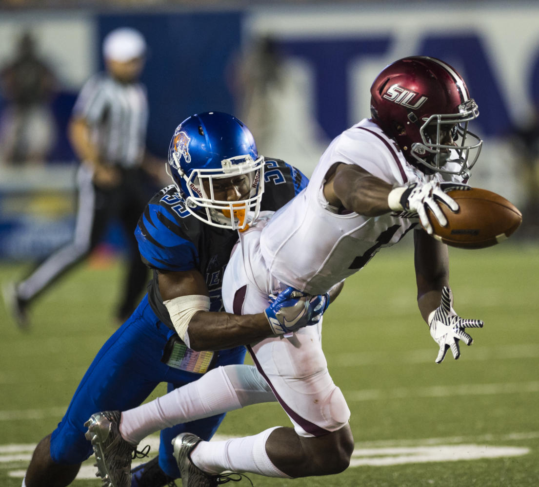 Junior wide receiver Raphael Leonard reaches with the ball as he's tackled by Tiger defense Saturday, Sept. 23, 2017 at the Liberty Bowl Memorial Stadium in Memphis, Tennessee. The Salukis fell to the University of Memphis Tigers, 44 - 31. (Dylan Nelson | @Dylan_Nelson99)