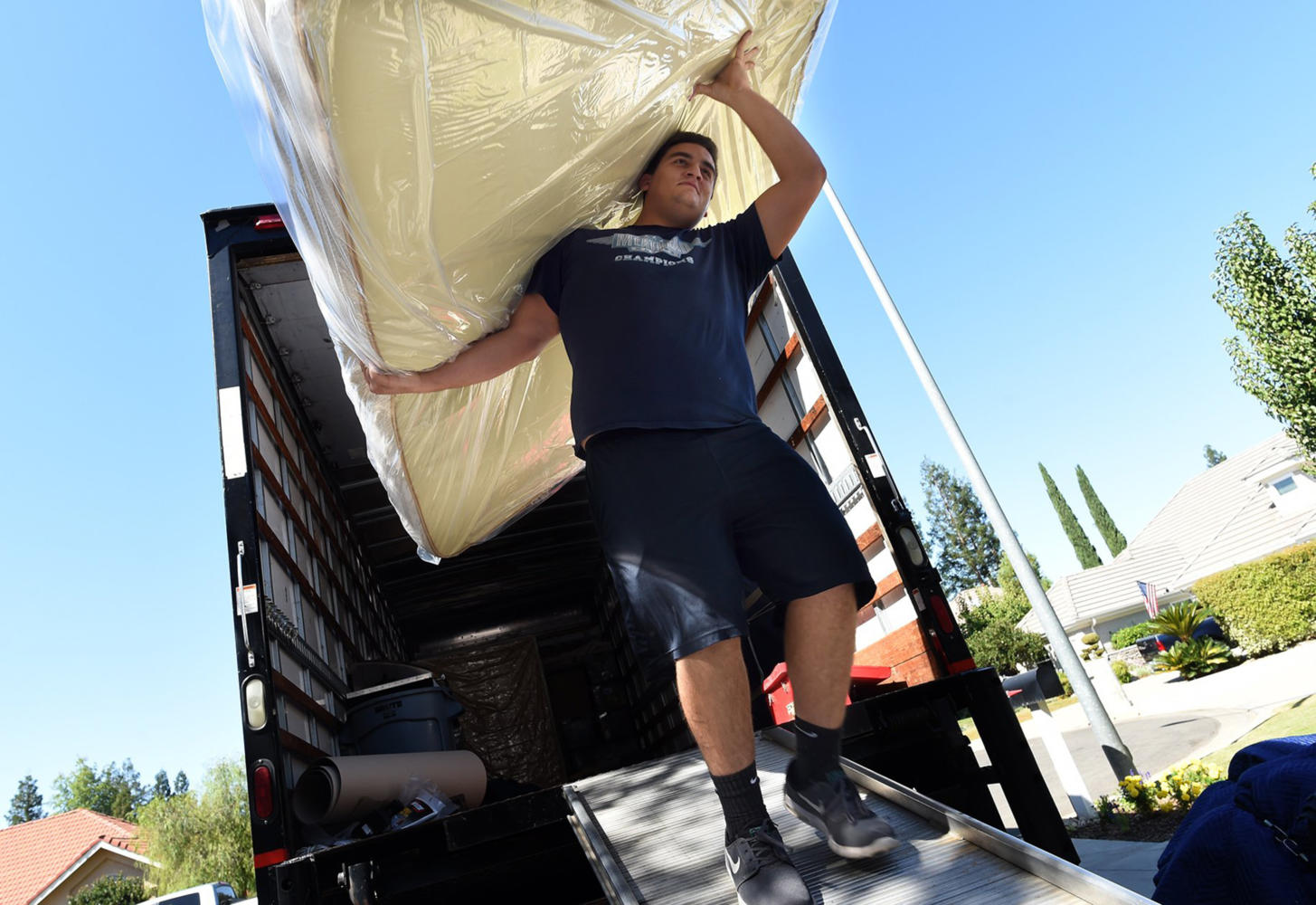 Meathead Movers worker Theo Stratigos, a former Bullard High football and rugby player, moves a bed into a home, Thursday, Sept. 28, 2017. (John Walker/Fresno Bee/TNS)