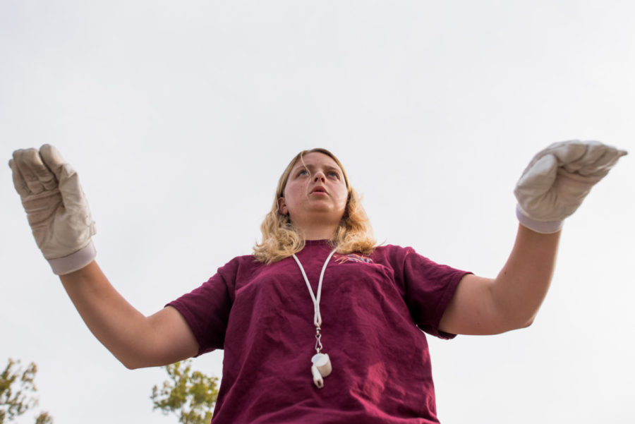 Junior anthropology major Madison Riden, of Nesbit, Mississippi, conducts during the Marching Salukis' halftime performance rehearsal Thursday, Oct. 5, 2017, outside Saluki Stadium.