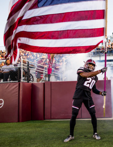 Junior wide receiver Jimmy Jones (20) waves the American flag Saturday, Sept. 30, 2017, as the Salukis rush into the stadium Saturday, Sept. 30, 2017 during the Salukis