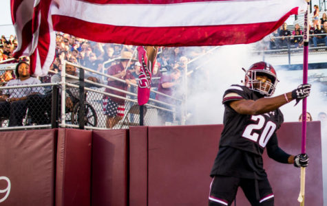 Junior wide receiver Jimmy Jones (20) waves the American flag Saturday, Sept. 30, 2017, as the Salukis rush into the stadium Saturday, Sept. 30, 2017 during the Salukis' match up against University of Northern Iowa Panthers. The Salukis fell to the Panthers , 24 - 17. (Dylan Nelson | @Dylan_Nelson99)