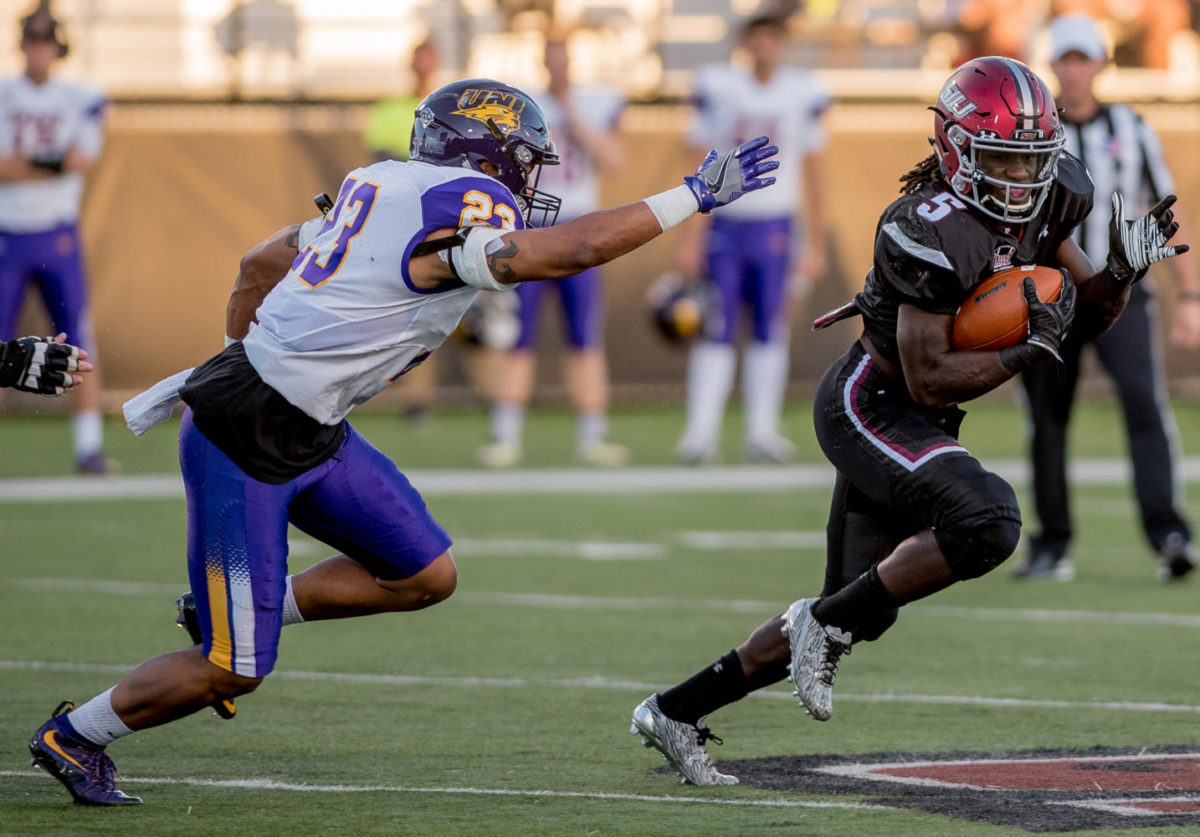SIU junior running back Daquan Isom (5) runs under pressure of University of Northern Iowa junior running back A.J. Allen Saturday, Sept. 30, 2017, during the Salukis' 24-17 loss against the University of Northern Iowa Panthers at Saluki Stadium. (Dylan Nelson | @Dylan_Nelson99)