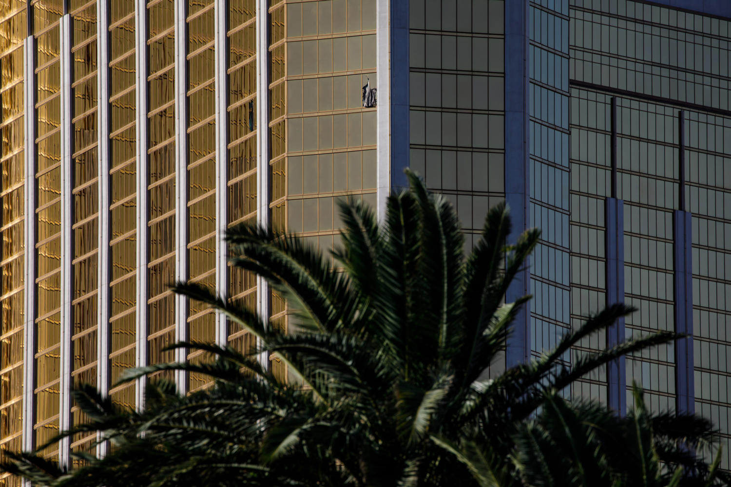 A curtain blows out of a broken window where a gunman opened fire from an upper story of Mandalay Bay resort on a country music festival across the street on the Las Vegas Strip on Sunday night, leaving at least 58 dead and more than 500 injured,  in Las Vegas, Nevada, on Oct. 2, 2017. (Marcus Yam/Los Angeles Times/TNS)