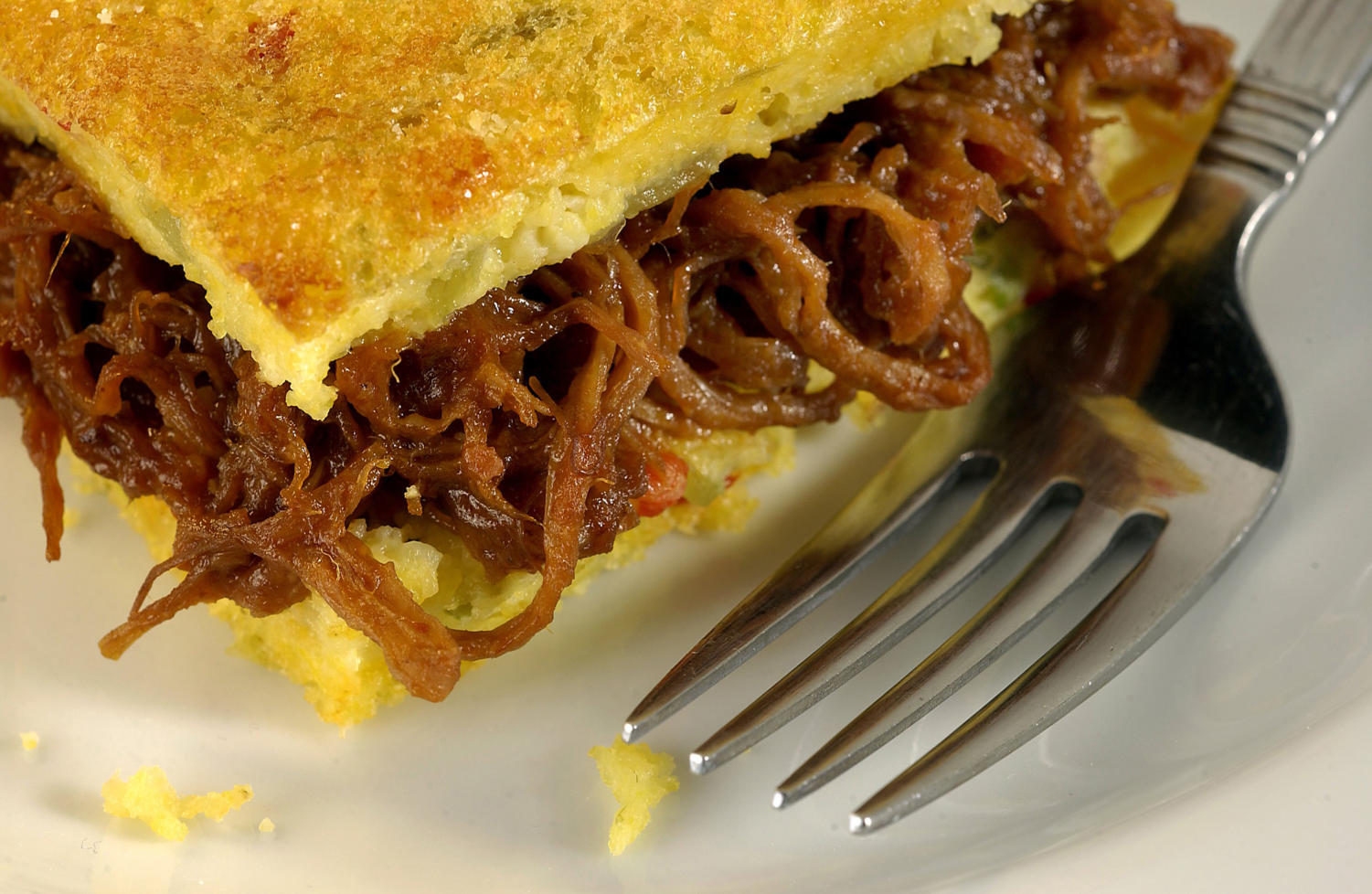 Barbequed pork is sandwiched between layers of corn bread that is bolstered with cheddar, corn kernels and jalapeno. (James F. Quinn/Chicago Tribune/TNS)