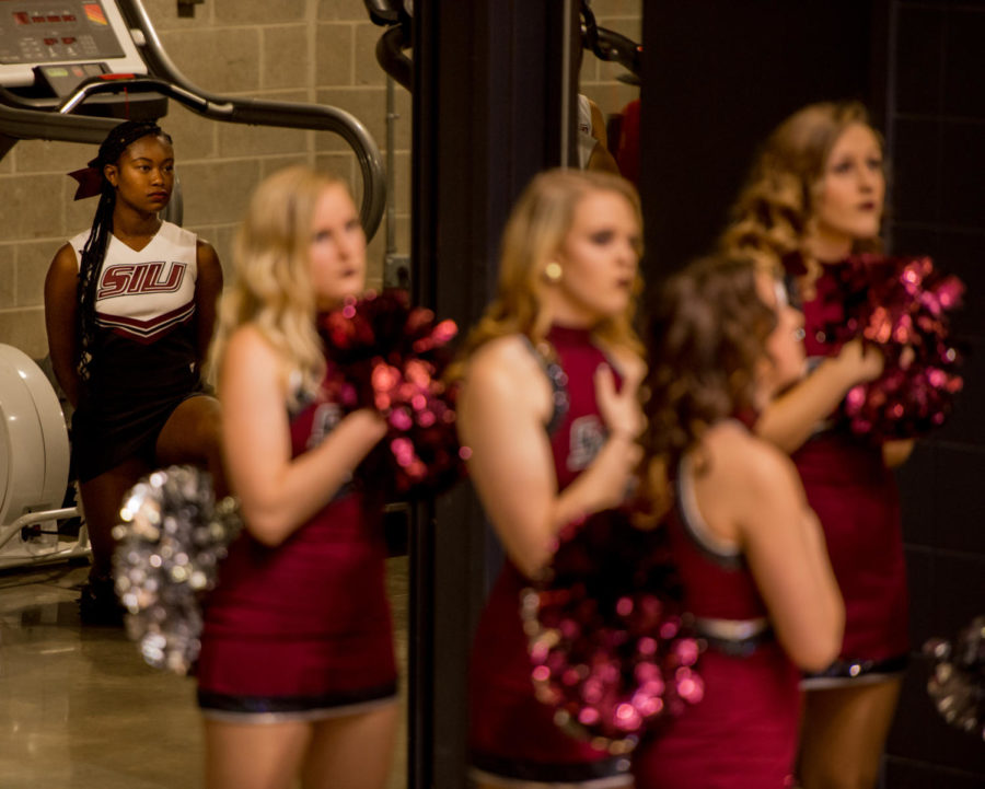Sophomore cheerleader Alaysia Brandy kneels behind Saluki Shakers during the national anthem Monday, Nov. 27, 2017, during the Salukis' loss to the SIU Edwardville Cougars at SIU Arena. A recent change in protocol put into place by SIU Athletics has removed the cheerleaders from the playing surface of sporting events during the national anthem. (Brian Muñoz | @BrianMMunoz)