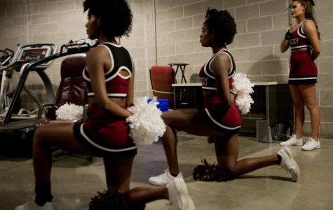 Cheerleaders Ariahn Hunt, left, and Alaysia Brandy, center, kneel during the national anthem Saturday, Nov. 18, 2017, before the Salukis' 69-64 win against the University of Illinois Springfield Prairie Stars at SIU Arena. (Brian Muñoz | @BrianMMunoz)