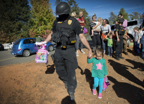 A special agent with the California Department of Justice walks a student from the Discovery Montessori school to her parents after being on lock-down because a suspect in the multiple shootings of officers in Sacramento and Placer County on Friday, Oct. 24, 2014. A suspect armed with a rifle left one Sacramento shefiff's deputy dead, a motorist gravely injured, and two Placer Conty sheriff's deputies wounded in a 30-mile crime spree. (Hector Amezcua/Sacramento Bee/MCT)
