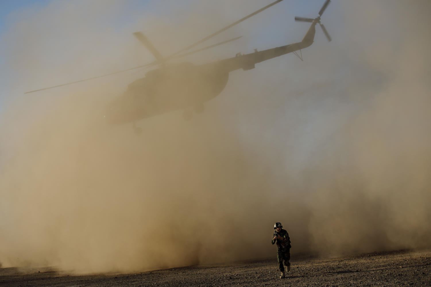 A soldier with the Afghan army leaves the landing site as an Afghan Mi-17 takes off during training near Camp Shorab, in Helmand Province. (Marcus Yam/Los Angeles Times/TNS)