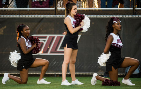 Sophomore psychology major Ariahn Hunt, left, and sophomore pre-med major Alaysia Brandy, both of Chiacgo, kneel during the national anthem Saturday, Sept. 30, 2017 before the Saluki's matchup against the University of Northern Iowa Panthers  at Saluki Stadium. (Brian Mu–oz | @BrianMMunoz)