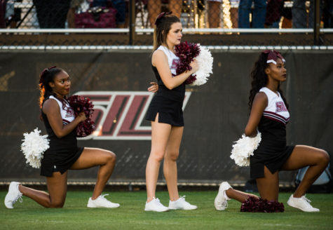 Sophomore psychology major Ariahn Hunt, left, and sophomore pre-med major Alaysia Brandy, both of Chiacgo, kneel during the national anthem Saturday, Sept. 30, 2017 before the Saluki