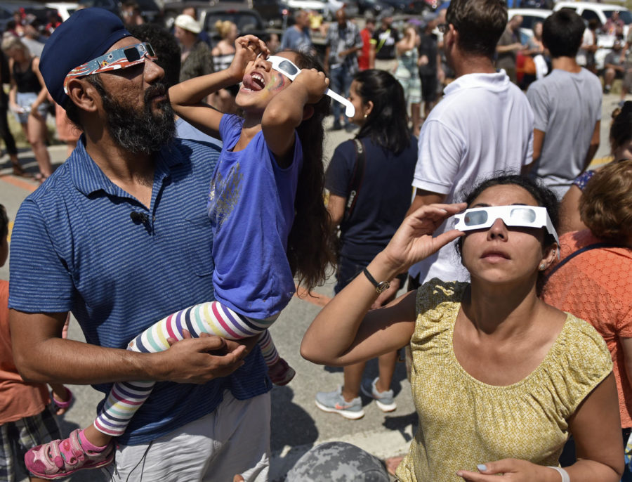 Roop Singh, Arya Singh, 5, and Minal Giri, all of Linkenshire, observe the solar eclipse through their eclipse glasses Monday, Aug. 21, 2017, in Makanda. Makanda, considered the crossroads of the Great American Eclipse, experienced the greatest total solar eclipse duration at over two minutes and 41 seconds. (Anna Spoerre | @annaspoerre)