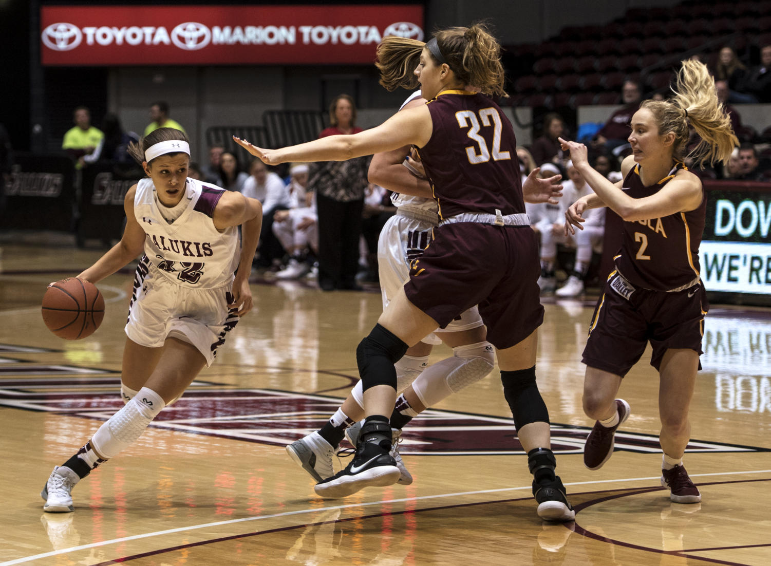 Senior guard Kylie Giebelhausen, 32, of east Peoria, dodges forward-center Kat Nolan's block, Friday, Jan. 19, 2018, during the Saluki's 62-46 win against Loyola University at SIU Arena. (Mary Newman | @MaryNewmanDE)