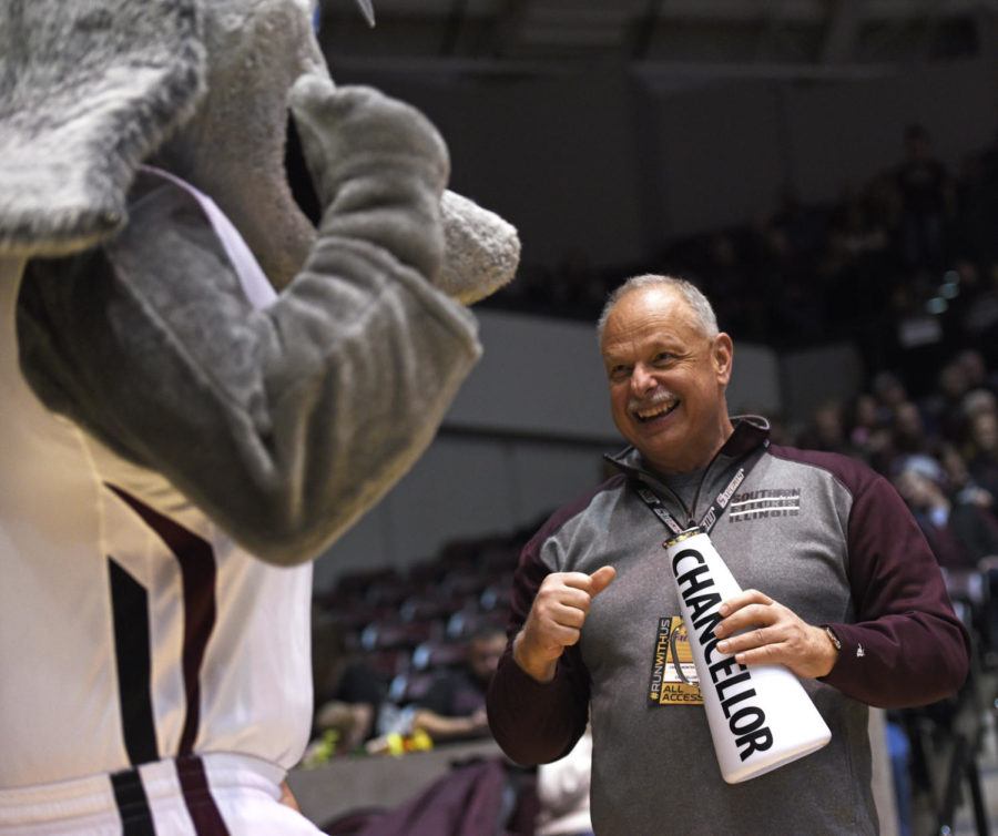 SIU Chancellor Carlo Montemagno interacts with Grey Dawg during SIU's 82-77 win against Indiana State on Wednesday, Jan. 24, 2018, at SIU Arena. (Anna Spoerre | @AnnaSpoerre)