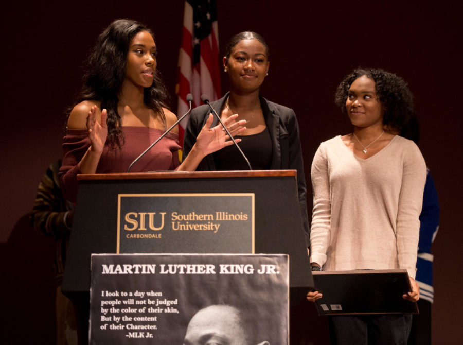 SIU cheerleaders Ariahn Hunt, Alasyia Brandy, both of Chicago, and Czarina Tinker, of Nashville, Tennessee, speak in front of a packed crowd Monday, Jan. 15, 2018, during the Carbondale NAACP Martin Luther King Jr. breakfast in the SIU Student Center. The girls were recognized for their willingness to protest police brutality by kneeling during the national anthem at sporting events. (Brian Muñoz | @BrianMMunoz)