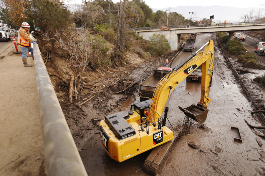Jose Gonzalez with Granite Construction directs crews from the Olive Mill Road bridge as they work to clear the 101 Freeway, which remains flooded with mud and debris under the Olive Mill Road bridge in Montecito, Calif. on Tuesday morning January 16, 2018. Officials hope to reopen the 101 freeway by Monday, January 22, 2018. A rain storm hit one week ago as the Santa Ynez Mountains deposited mud and debris into Montecito neighborhoods, killing more than 20 people. (Al Seib/Los Angeles Times/TNS)