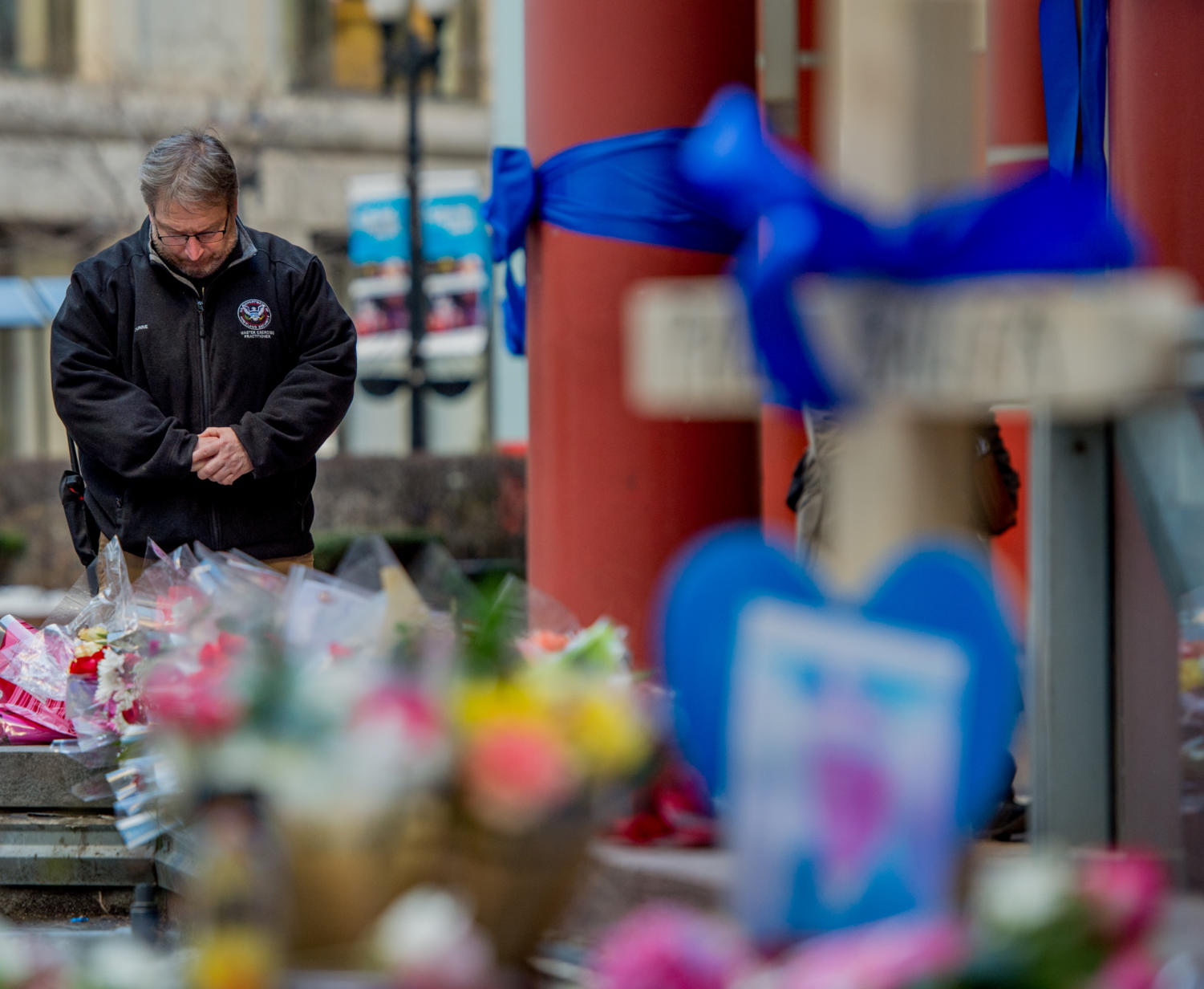 Robert Dunne, an Office of Homeland Security agent from Chicago, pays his respects at the site of Chicago police commander Paul Bauer's death, Friday, Feb. 16, 2018, outside of Thompson Center in Chicago, Illinois. Bauer was shot to death after chasing a man fleeing from tactical officers, according to the Chicago Tribune.