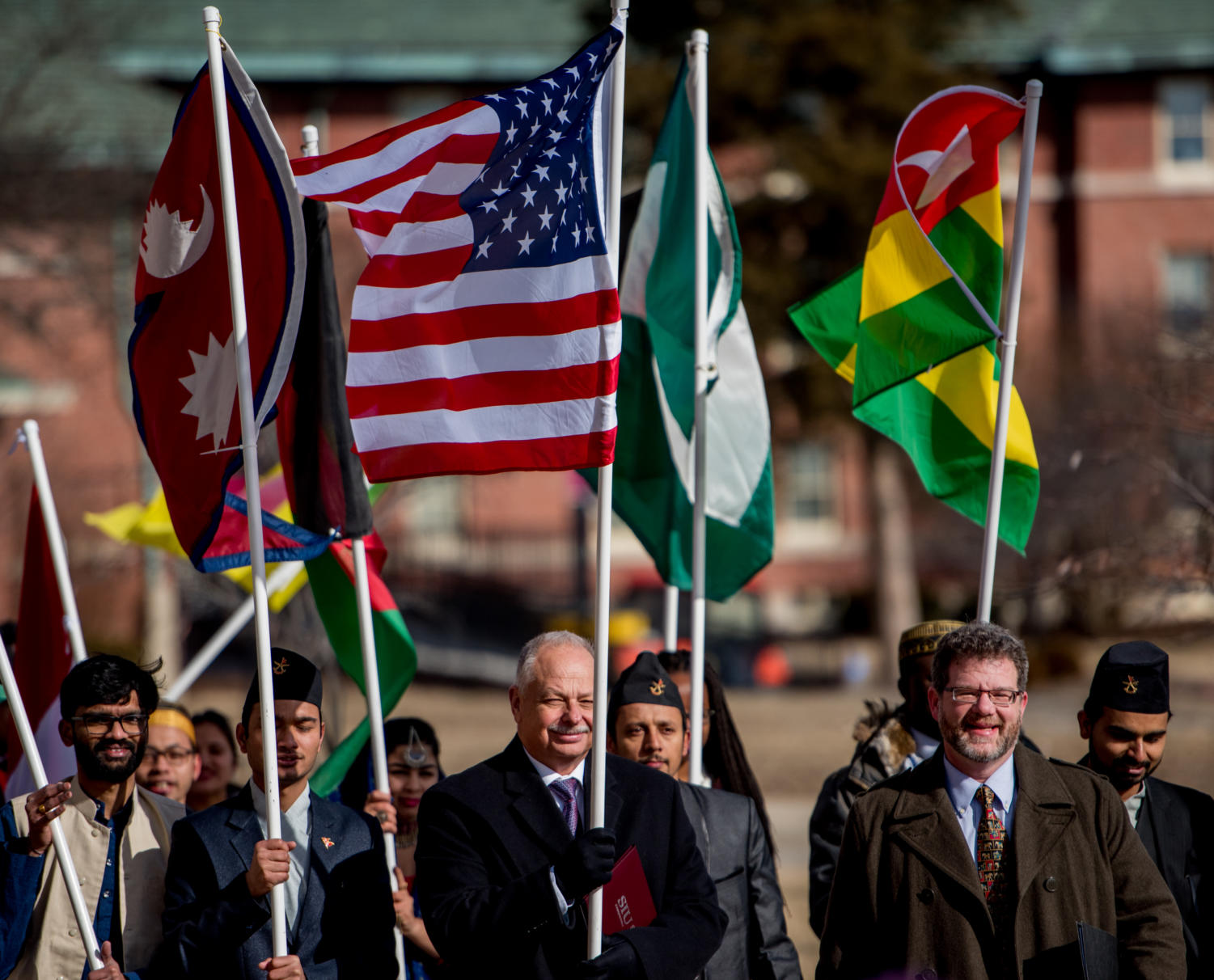 Chancellor Carlo Montemagno, center, carries the American flag from Anthony Hall to the student center on Monday, Feb. 5, 2018, during the the International Parade of Flags. (Brian Munoz | @BrianMMunoz)