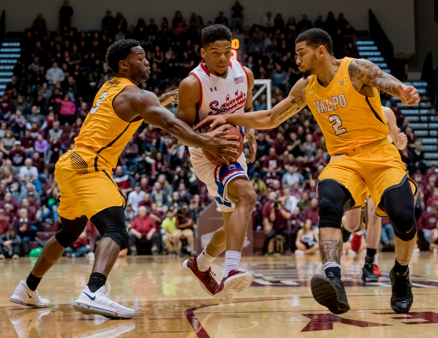 Sophomore guard Aaron Cook attempts to get past Valparaiso guard Max Joseph, far left, and Valparaiso guard Tevonn Walker Saturday, Feb. 3, 2018, during the Salukis' 65 - 59 win against the Valparaiso Crusaders at SIU Arena. (Brian Munoz | @BrianMMunoz)