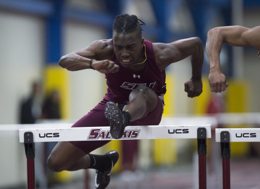 Junior sprinter Warren Hazel jumps over a hurdle during a invitational meet on Saturday, Feb. 3, 2018  at student recreational center. (Dylan Nelson | @Dylan_Nelson99)