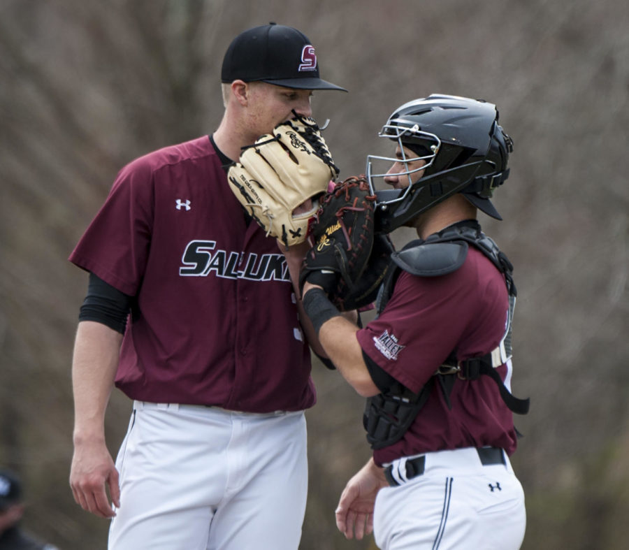 From left: Senior Michael Baird consults sophomore Austin Ulick, 17, of Washington, Friday, March 23, 2018, during the Saluki's 2-6 loss against University of California, Irvine at Itchy Jones Stadium. (Mary Newman | @MaryNewmanDE)