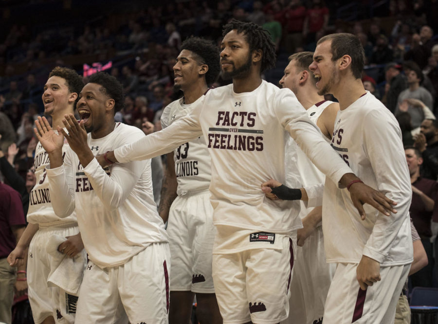 Members of the Saluki men's basketball team celebrate Friday, March. 3, 2018, during the Salukis' 67-63 win against the Missouri State Bears at the MVC tournament in St. Louis. (Athena Chrysanthou | @Chrysant1Athena)