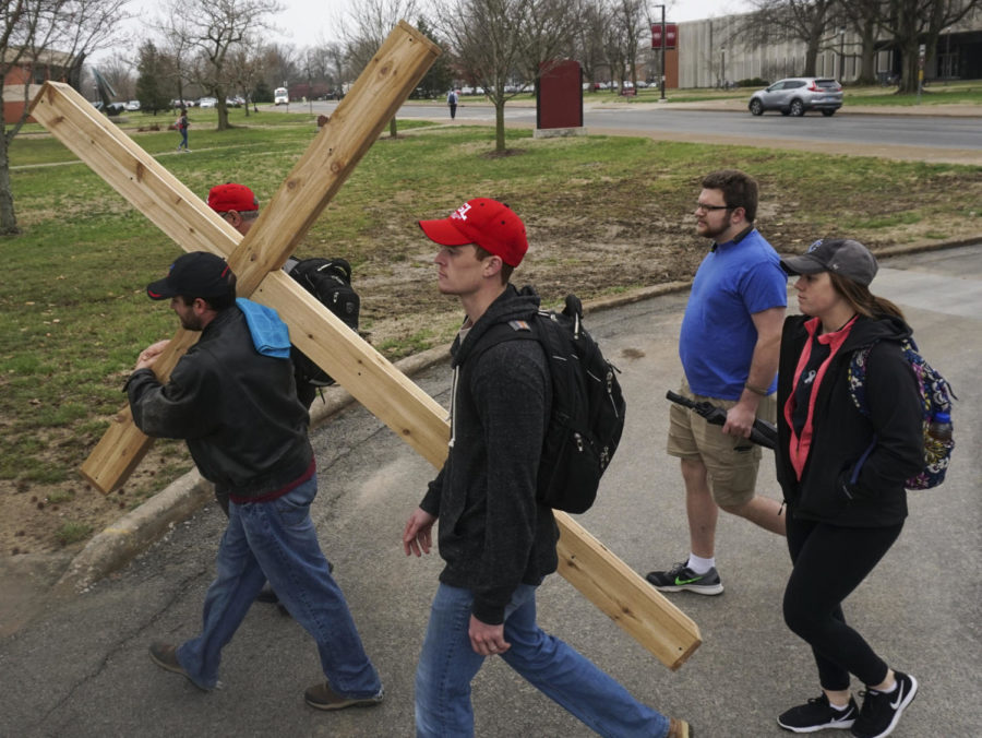 Patrick Hogge, left, a senior studying aviation technology from Taylorville, carries the cross along with members of the Baptist Collegiate Ministry to the Morris Library on Tuesday, March 27, 2018, during their annual crosswalk event leading up to Easter Sunday.