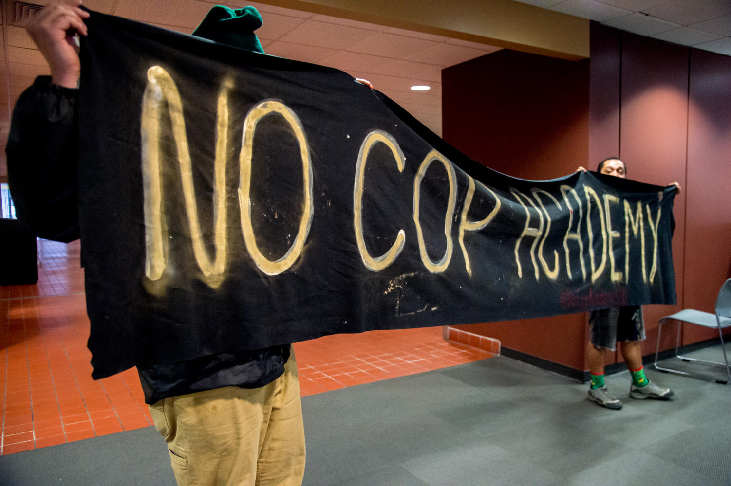 Demonstrators hold up a banner Thursday, March 29, 2018, during a demonstration against a proposed police academy at Southern Illinois University in the student center. (Brian Munoz   @BrianMMunoz)