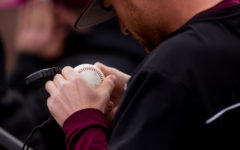 A Saluki baseball staffer inspects a game ball Saturday, March 10, 2018, during the Salukis' 7-2 victory against the Northern Illinois University Huskies at Itchy Jones Stadium. (Brian Munoz | @BrianMMunoz)