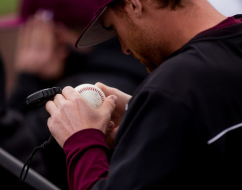 A Saluki baseball staffer inspects a game ball Saturday, March 10, 2018, during the Salukis