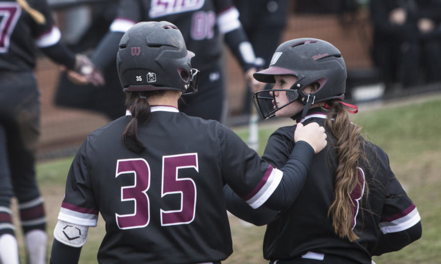 Saluki softball Pitcher Megan Brown, left, congratulates Outfielder Susie Baranski after a play Sunday, March 25, 2018, during the Blackout Cancer game, where the Salukis took a 6-3 win against Illinois State University, at Charlotte West Stadium. (Corrin Hunt   @CorrinIHunt)