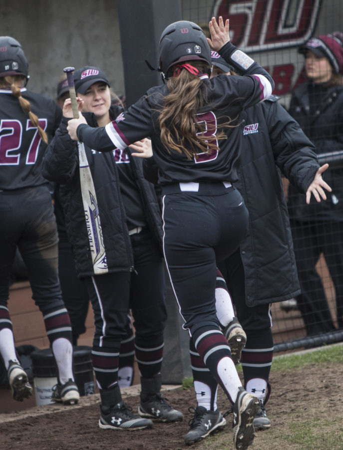 Saluki sophmore Susie Baranski gets congratulated by her teammates on her way into the dugout Sunday, March 25, 2018, during the Blackout Cancer game, where the Salukis took a 6-3 win against Illinois State University, at Charlotte West Stadium. (Corrin Hunt   @CorrinIHunt)