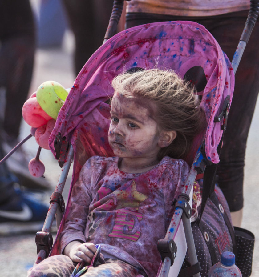 Kennedy Tilley, 3, of DuQuion, sits in her color covered stroller, Saturday, April 21, 2018, during the Color Fun Run for the Autism Society of Southern Illinois at Southern Illinois University. (Corrin Hunt   @CorrinIHunt)