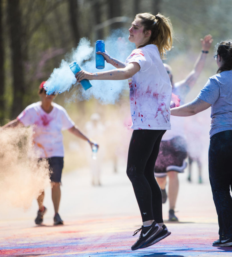 Carrie Allen, a volunteer for the color run, dances while throwing color, Saturday, April 21, 2018, during the Color Fun Run for the Autism Society of Southern Illinois at Southern Illinois University. (Corrin Hunt   @CorrinIHunt)