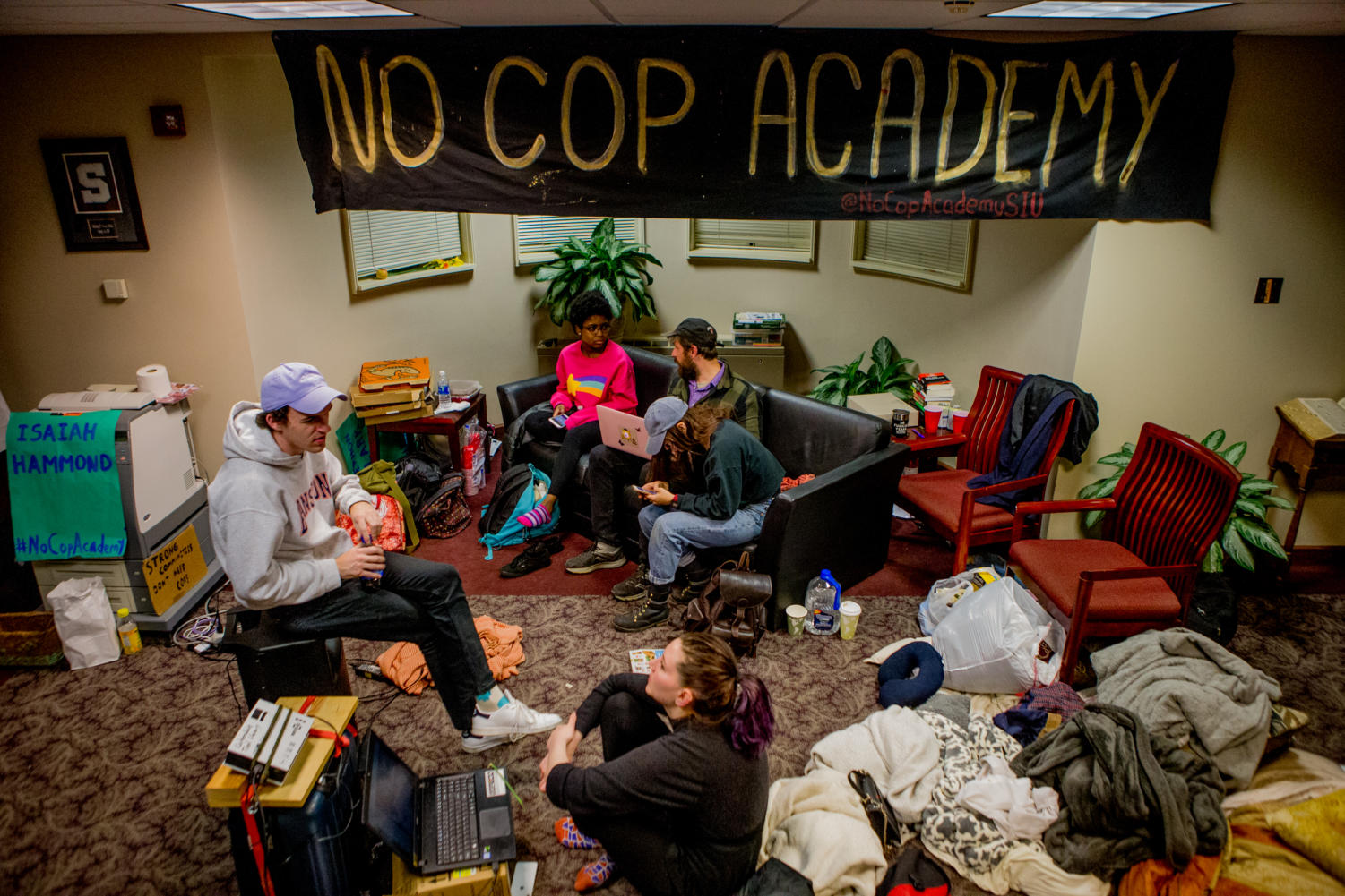 Demonstrators talk with each other on community Friday, April 6, 2018, during an occupation of SIU Chancellor Carlo Montemagno's office in Anthony Hall. The occupation followed a march through campus the previous day in protest of the proposed police academy at the Southern Illinois University Carbondale campus. (Brian Munoz | @BrianMMunoz)