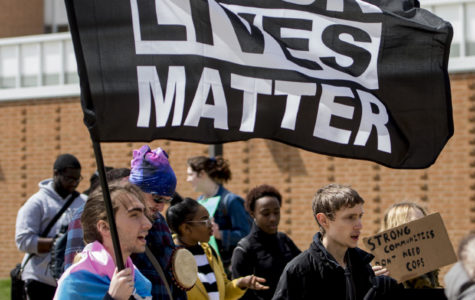 Michael Thornton, a sophomore from Naperville studying digital media arts and animation, carries a Black Lives Matter flag in front of the student center Thursday, April 5, 2018, during a protest on the proposed police academy at the Southern Illinois University Carbondale campus. (Brian Munoz | @BrianMMunoz)