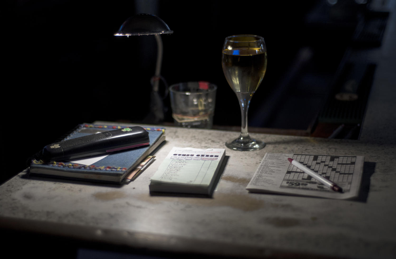 "A glass of white wine, a crossword puzzle, a notebook, an order-taking pad, and a phone sit in ""Gwen's spot"" after PK's reopened, Monday, June 11, 2018. PK's closed briefly after the death of beloved owner Attie Gwendolyn Hunt Saturday, June 9, 2018."