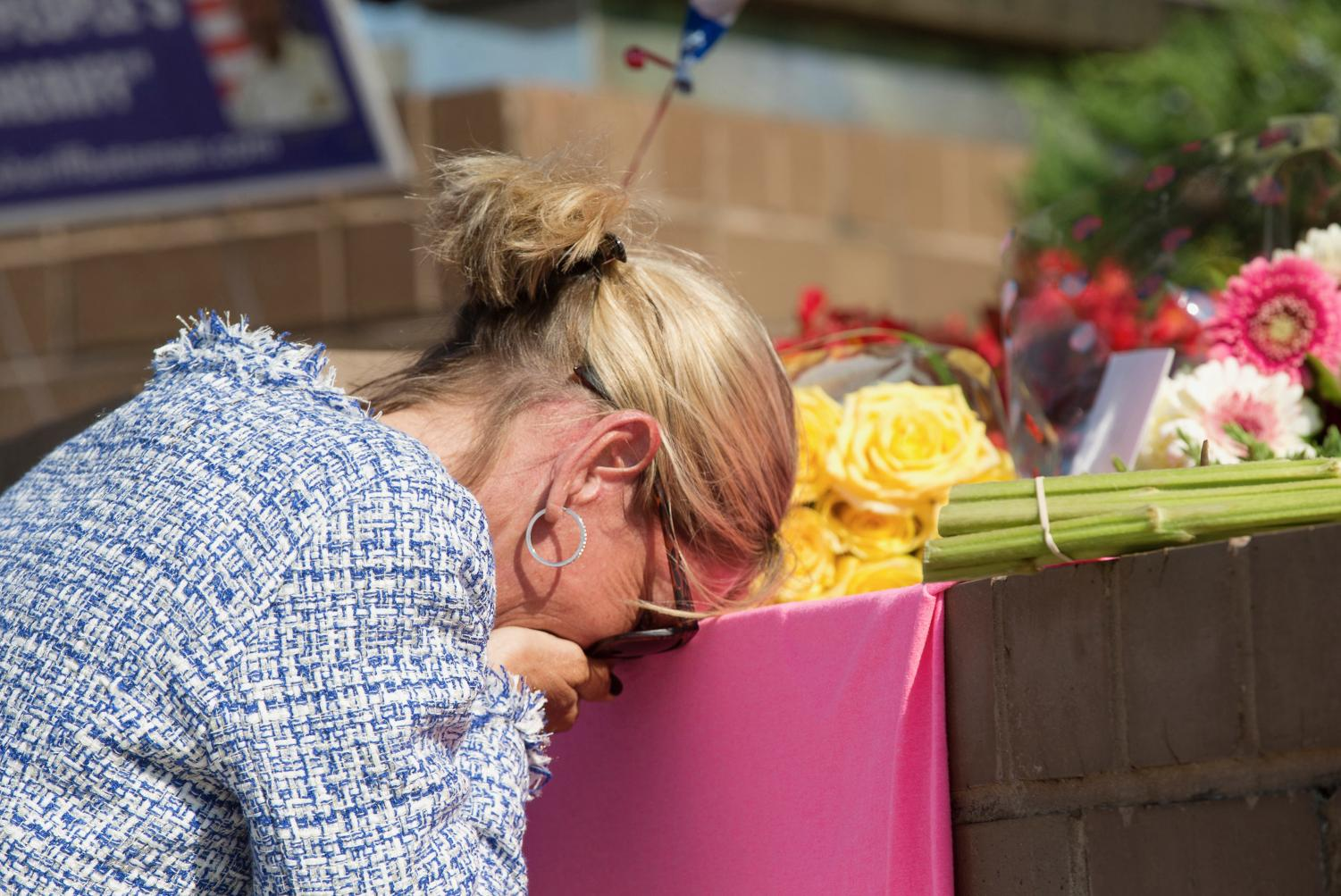 An unidentified mourner grieves at a small memorial set up at the entrance of 888 Bestgate Road on Friday, June 29, 2018. A gunman blasted his way into the Capital Gazette newsroom in Annapolis with a shotgun Thursday afternoon, killing five people and injuring two others, authorities said. (Jen Rynda/Capital Gazette/TNS)