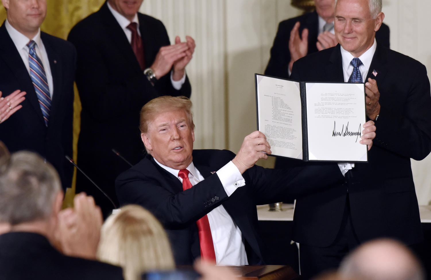 President Donald Trump holds a signed National Space Directive to establish a Space Traffic Management program to address the congestion of satellites and space vehicles in Earth's orbit during a meeting with the National Space Council on Monday, June 18, 2018 in the East Room of the White House, in Washington, D.C. (Olivier Douliery/Abaca Press/TNS)