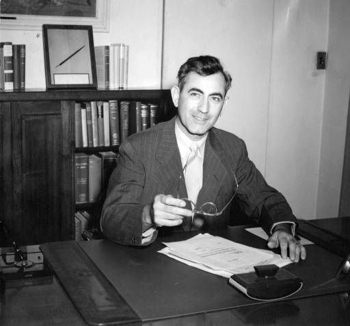 Southern Illinois University President Delyte W. Morris at his desk in the inner office of the President's Office when it was located in Shryock Auditorium. This is during his first year as President of SIU.