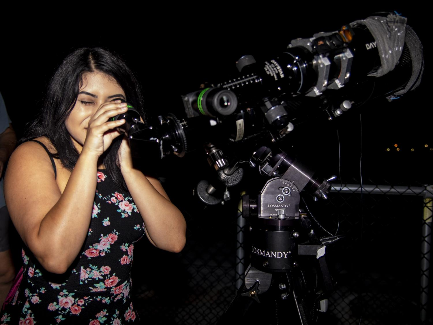 Jenifer Ruiz, a senior studying radiation therapy, of Zion looking at the planets and stars through a telescope on the roof of Neckers during the physic department's public astronomy viewing, Sunday, Aug. 2018. (Allie Tiller | @allietiller_de)