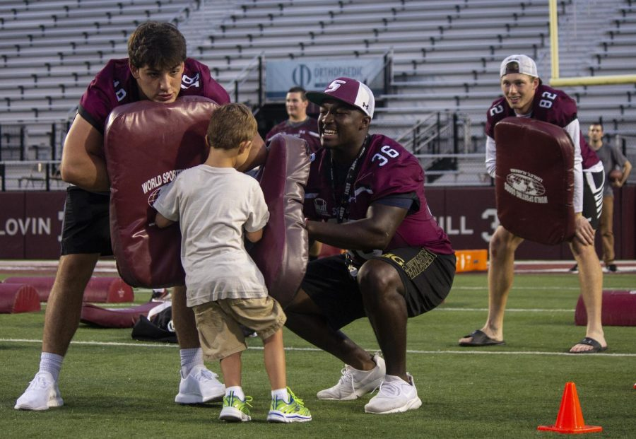 Nic Baker (left), a freshman, of Rochester, Tremayne Lee (center), a freshman, of Springfield, and Skyler Peterman (right), a sophomore, of Carbondale, assist in the football drills on Thursday, Aug. 23, 2018, at the Saluki Football Fan Fest, at Saluki Stadium.