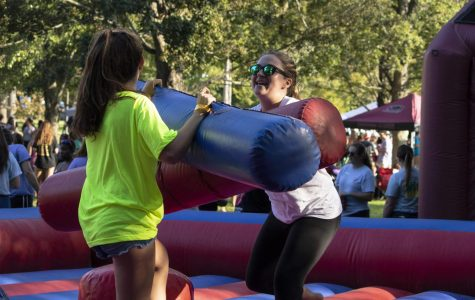 Jacqueline Zarcone (right), a junior studying psychology and language, and Rebecca Tompkins (left), a senior studying dental hygiene, both of Sigma Kappa, battling one another in the gladiator duel inflatable at the Greek Barbecue, Monday, Aug. 27, 2018. (Allie Tiller | @allietiller_de)