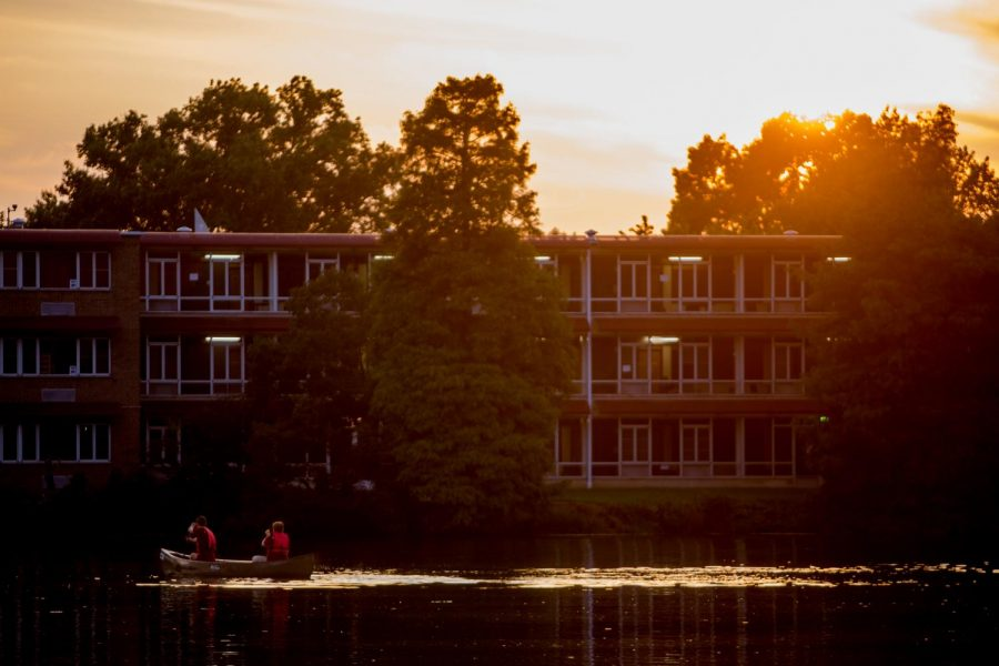 Students paddle in front of the Thompson Point dorms on Thursday, Aug. 16, 2018, during