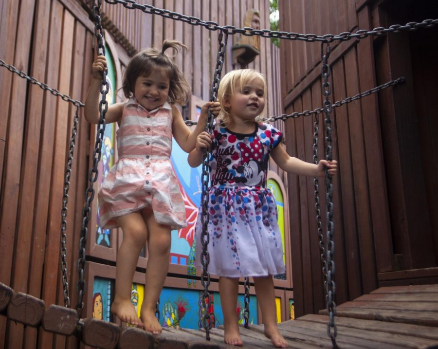 "Sequoia and Willow Fox, both 3, jump on a bridge together. Willow Fox's mother, Raine Fox, said Willow ""gets to meet other little kids, and there's all these little mazes and passage ways, it's just amazing"", Wednesday, Sept. 12, 2018, at Castle Park in Carbondale. (Isabel Miller 