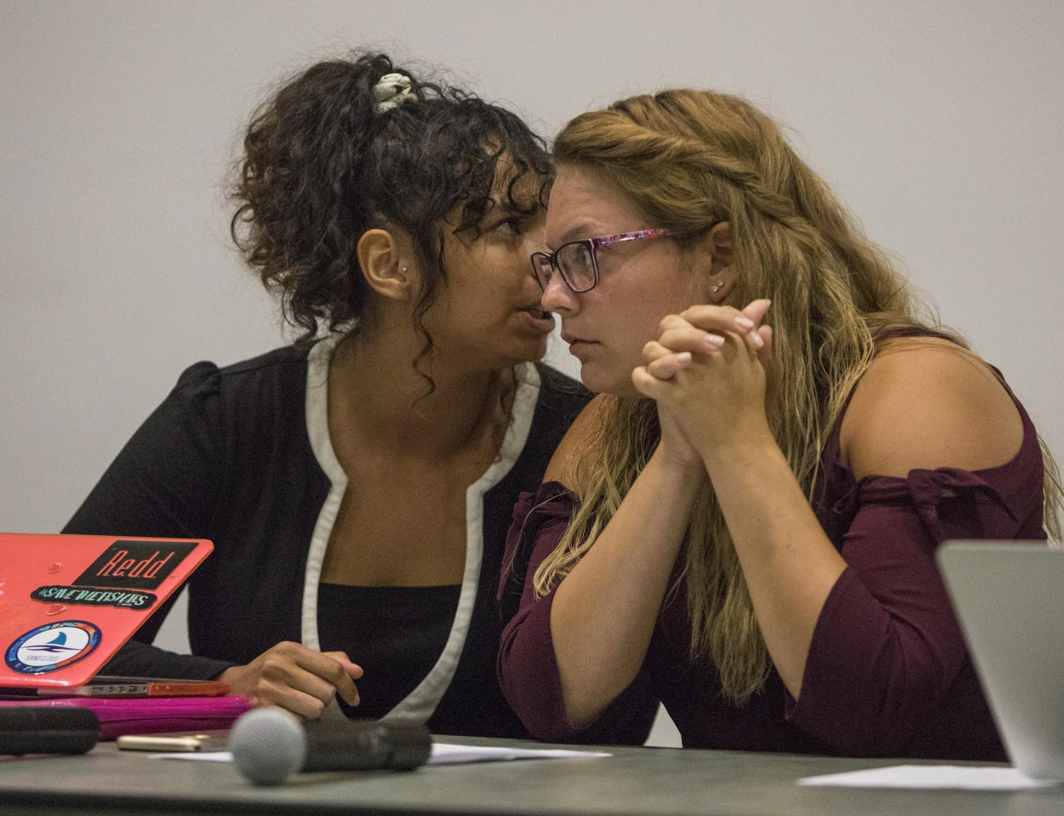 Sophia Julio, a senior studying Anthropology (left) and Jordan Coutcher, a sophomore studying Political Science, whisper while a member of the affirmative side speaks, Monday, Sept. 17, 2018, during the 8th Annual Constitution Day Debate, in Morris Library. (Corrin Hunt | @CorrinIHunt)