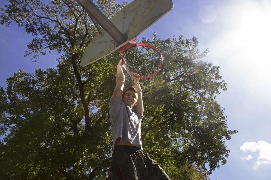 """Sean Thornton, 19, of Oak Lawn, hangs from the rim with a smile on his face, Tuesday, Oct. 2, 2018, on a basketball court near West Campus. """"In college it's important to find something that relieves you of stress in a healthy way, basketball is my escape."""" Thornton said. (Chase Jordan 