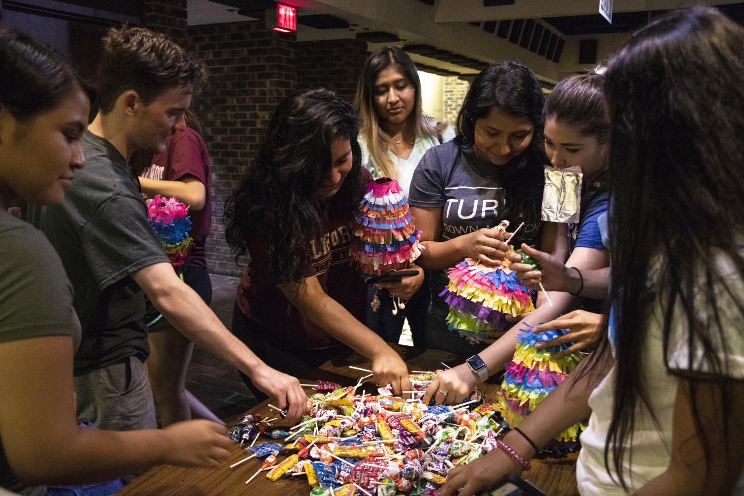 SIU+students+grab+candy+from+a+pile+to+put+in+pinatas+they+made+at+the+Student+Center+Craft+Shop+during+day+two+of+the+pinata+event+for+Hispanic+Latino+Heritage+Month%2C+Friday%2C+Oct.+5%2C+2018.+%E2%80%9CYou+fill+%5Bthe+pinata%5D+with+good+stuff+because+that%E2%80%99s+things+that+you+want+in+life%2C%E2%80%9D+Celeste+Orozco%2C+a+junior+studying+forestry%2C+said.+%E2%80%9CIt+is+normally+hung+because+it+is+supposed+to+be+up+in+the+sky%2C+like+the+heavens%2C+so+you%E2%80%99re+looking+up+and+it%E2%80%99s+about+faith%2C%22+Orozco+said.+%22So%2C+just+keep+going+and+eventually+when+you+break+through+all+the+barriers%2C+good+things+will+come+of+it+and+that+is+the+candy+part+of+it.%E2%80%9D+%28Allie+Tiller+%7C+%40allietiller_de%29