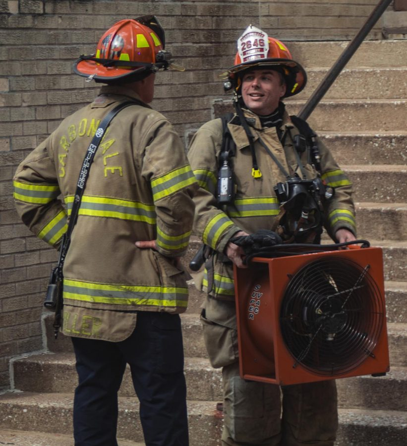 Two firemen talk while bringing equipment out of the building, Tuesday, Oct. 9, 2018, after a kitchen fire at Quadrangles Apartments in Carbondale. (Nick Knappenburger | @DeKnappenburger)