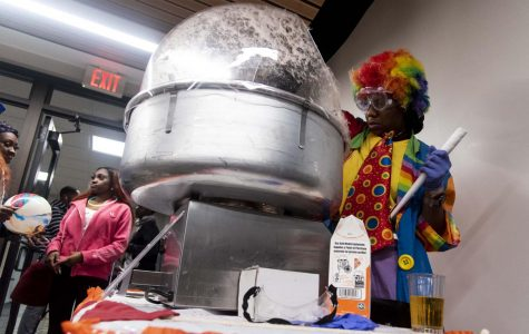 "Daryah Ireland, a sophomore studying business management, 19, making cotton candy in the Lentz dining hall while dressed as a clown for their carnival-themed night, Thursday, Oct. 25, 2018. ""I think this benefits the students because it gives them the feeling of being at home."" Ireland said. ""Cotton candy is like fun and there's fun stuff to do. It's always good to switch up the type of food and the style that we have from the, like, everyday.""  (Allie Tiller 