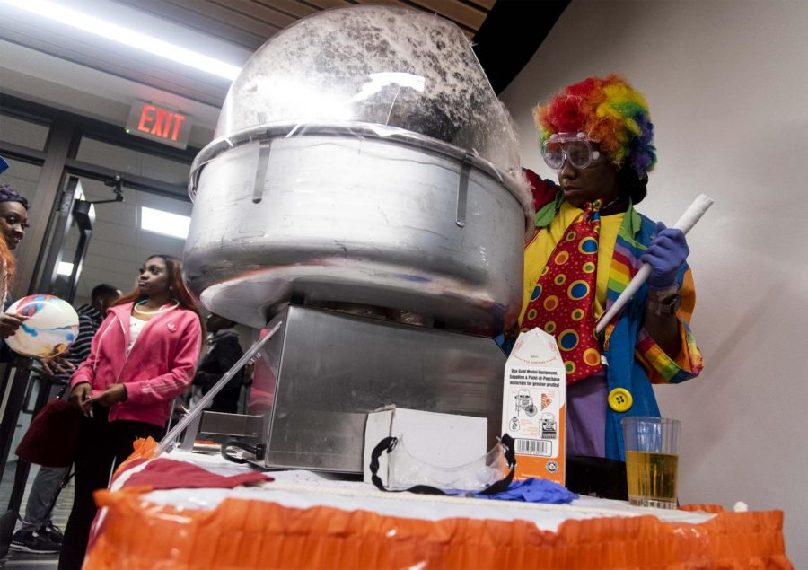 """Daryah Ireland, a sophomore studying business management, 19, making cotton candy in the Lentz dining hall while dressed as a clown for their carnival-themed night, Thursday, Oct. 25, 2018. """"I think this benefits the students because it gives them the feeling of being at home."""" Ireland said. """"Cotton candy is like fun and there's fun stuff to do. It's always good to switch up the type of food and the style that we have from the, like, everyday.""""  (Allie Tiller 